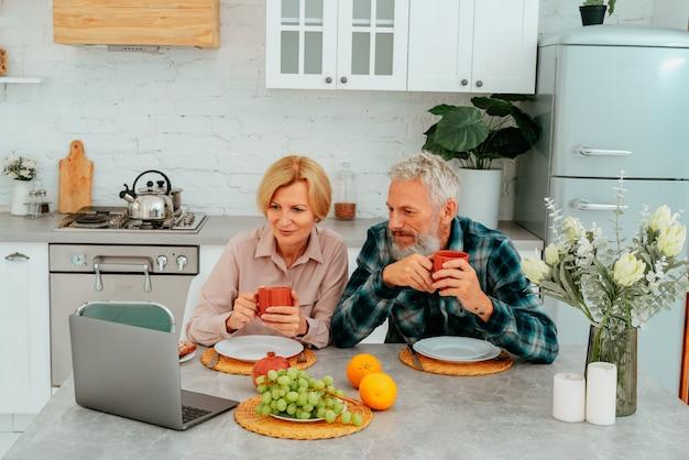 Casal toma café da manhã em casa e assiste algo em um laptop