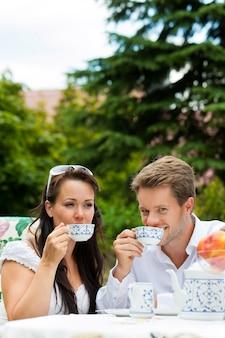 Casal tomando café da manhã com café no jardim
