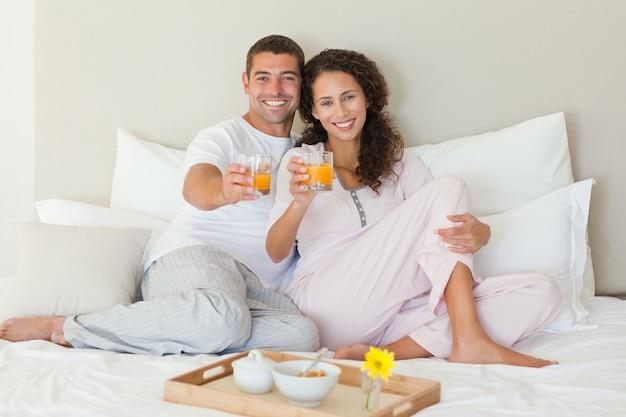 Casal tomando café da manhã na cama em casa