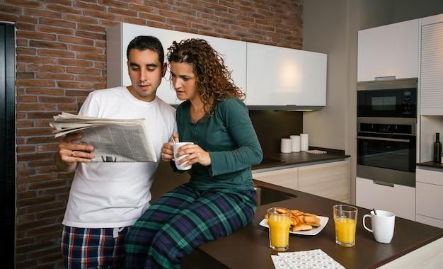 Casal tomando café da manhã na cozinha e lendo jornal