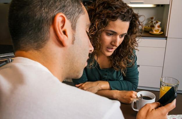 Casal tomando café da manhã na cozinha e olhando para o celular