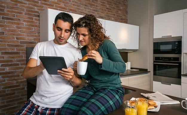 Casal tomando café da manhã na cozinha e olhando para o tablet
