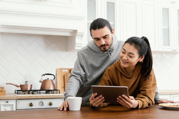 Casal tomando café da manhã na cozinha e usando um tablet