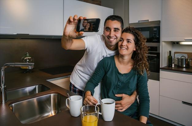 Casal tomando café da manhã na cozinha enquanto tira uma selfie