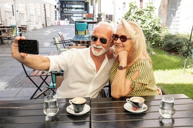 Casal tomando café e tomando uma selfie