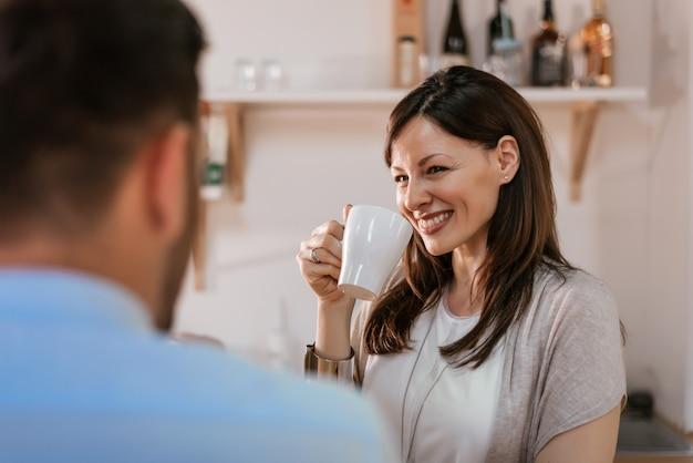 Casal tomando café juntos em casa.