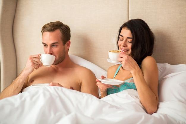 Casal tomando café na cama.
