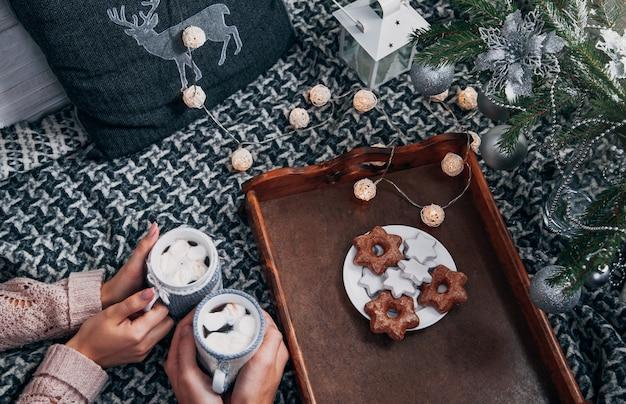 Casal tomando chocolate quente com biscoitos debaixo da árvore de natal