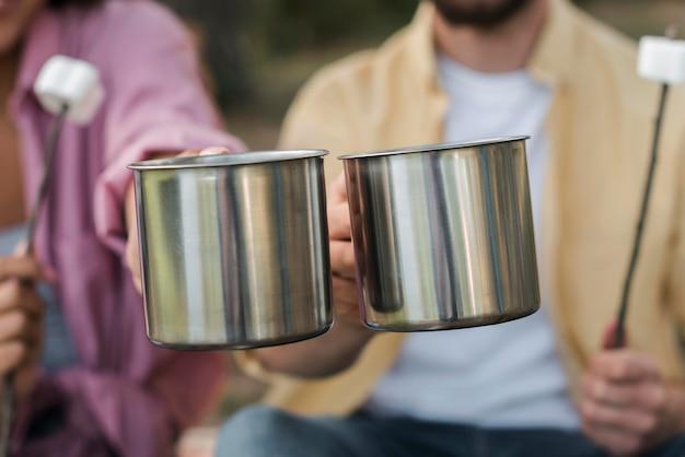 Casal tomando marshmallows e bebidas quentes enquanto acampa
