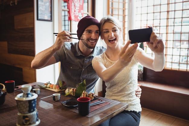 Casal tomando selfie enquanto come sushi
