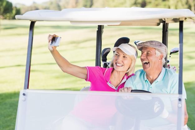 Casal tomando selfie enquanto está sentado no carrinho de golfe