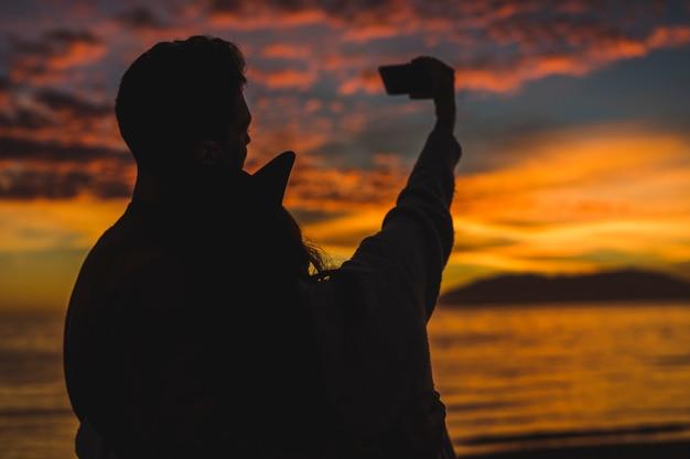 Casal tomando selfie na costa do mar à noite