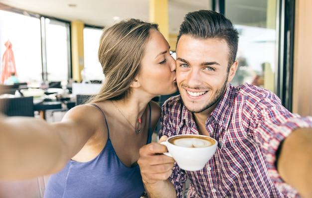 Casal tomando selfie na hora do café da manhã