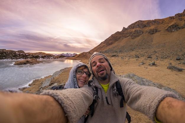Casal tomando selfie nas montanhas pela lente olho de peixe