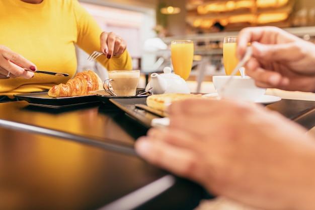 Casal tomando um café da manhã no café, ela está comendo um croissant, ambos estão bebendo um suco de laranja.