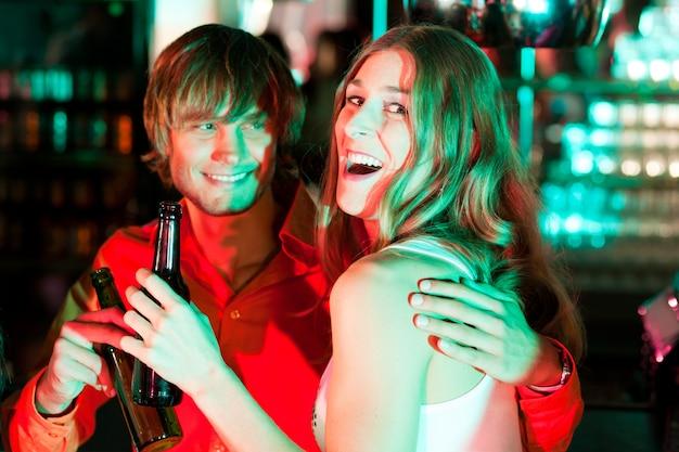 Casal tomando uma bebida no bar ou clube