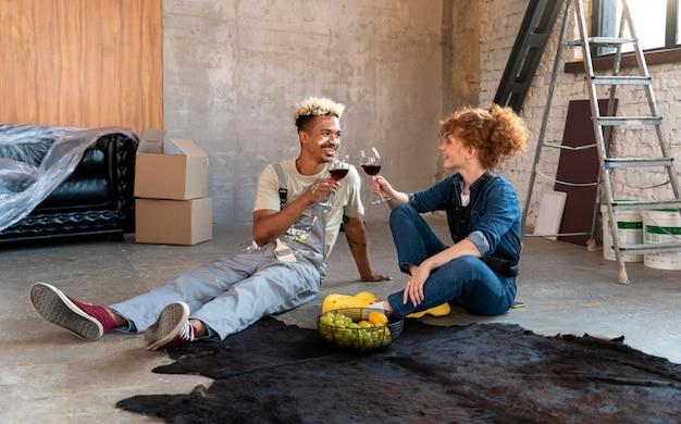 Casal tomando vinho depois de se mudar para sua nova casa