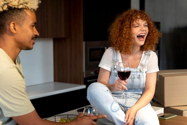 Casal tomando vinho na cozinha de sua nova casa