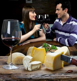 Casal tomando vinho tinto e comendo queijo no restaurante