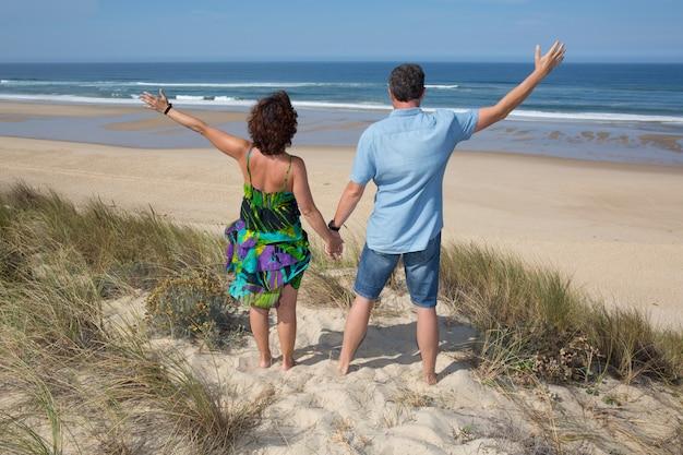 Casal torcendo na praia viaja de férias. visão traseira