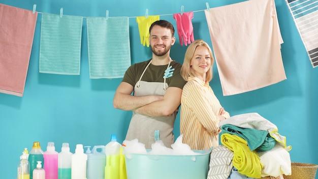 Casal trabalhador está pronto para ajudá-lo com lavanderia. serviço de lavanderia