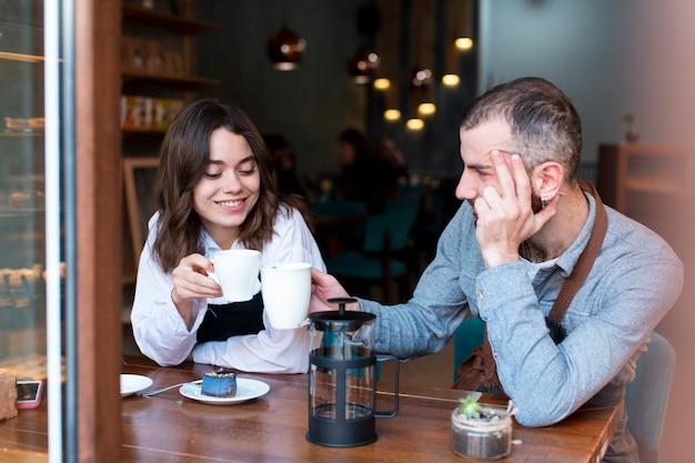 Casal trabalhando na cafeteria e bebendo café