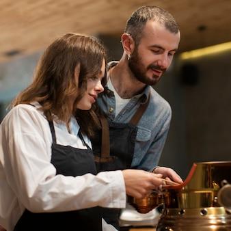 Casal trabalhando na máquina de café