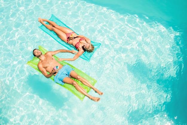 Casal tranquilo em lilos segurando coquetéis na piscina