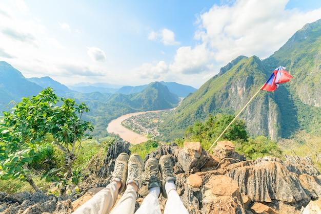 Casal trekking bota no topo da montanha em nong khiaw vista panorâmica sobre o vale do rio nam ou laos