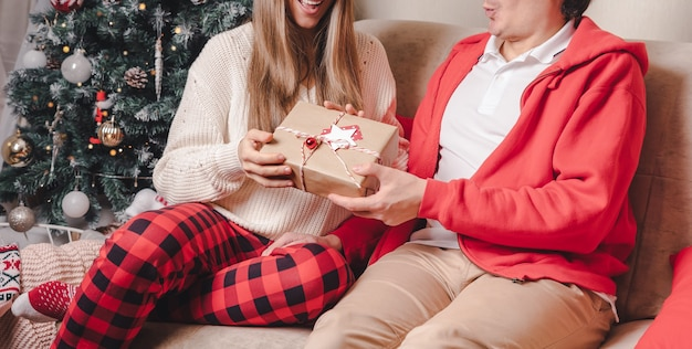 Casal trocando presentes perto da árvore de natal decorada.