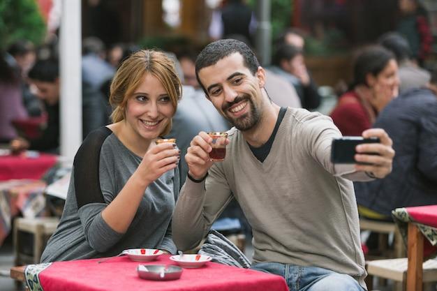 Casal turco tomando selfie enquanto bebia cay, chá tradicional