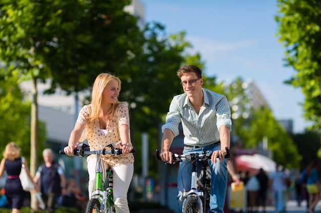 Casal urbano andando de bicicleta no tempo livre na cidade