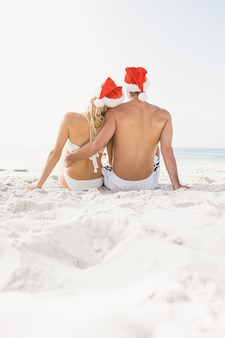 Casal usando chapéu de papai noel na praia
