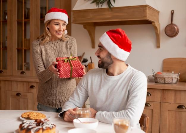 Casal usando chapéus de natal dentro de casa