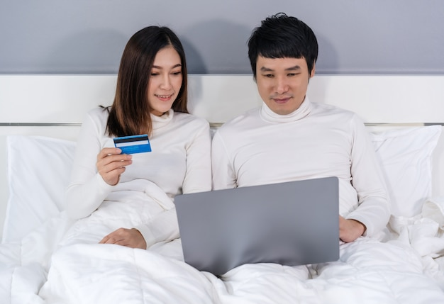 Casal usando computador portátil para compras on-line com cartão de crédito na cama
