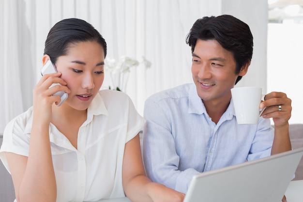 Casal usando laptop com mulher falando no telefone