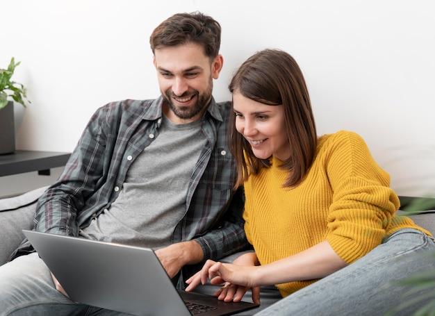 Casal usando laptop em casa