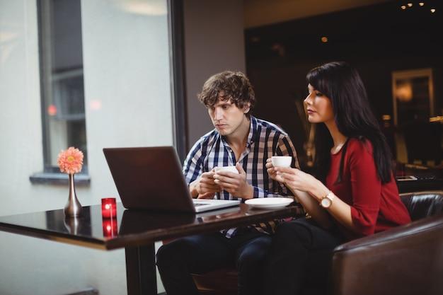 Casal usando laptop enquanto toma café