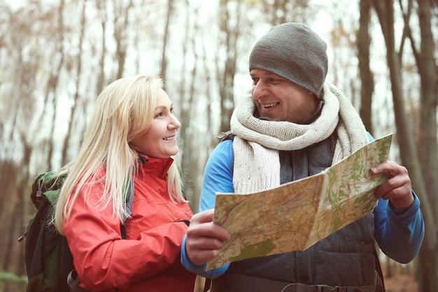 Casal usando mapa de papel durante uma caminhada