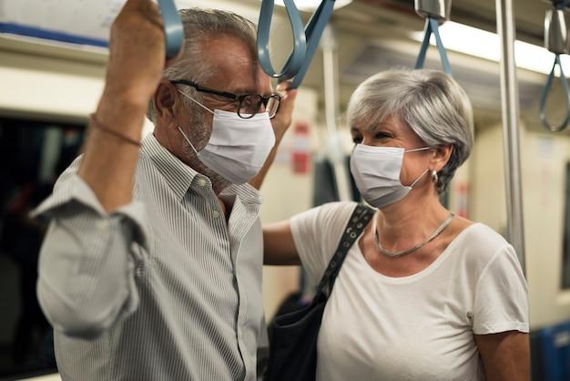 Casal usando máscaras em trem no novo normal