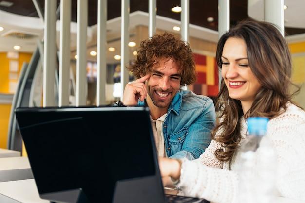 Casal usando o laptop no restaurante.