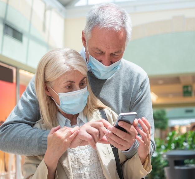 Casal usando seu smartphone juntos durante pandemia de coronavírus