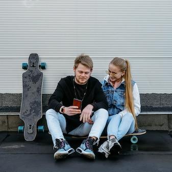 Casal usando smartphone ao ar livre