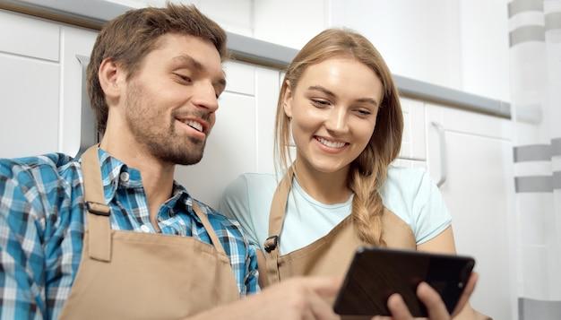 Casal usando smartphone enquanto descansa após limpar a cozinha