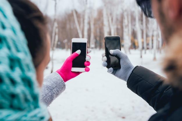 Casal usando smartphone no inverno com luvas para telas sensíveis ao toque