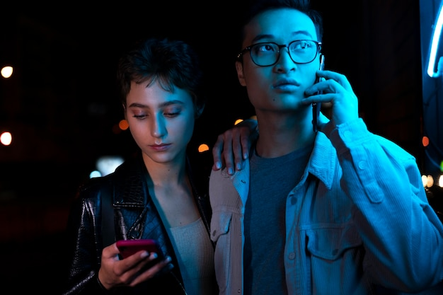 Casal usando smartphones à noite com luz de néon azul