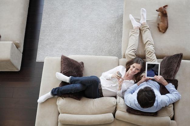 Casal usando tablet digital em casa sentado no sofá, vista de cima