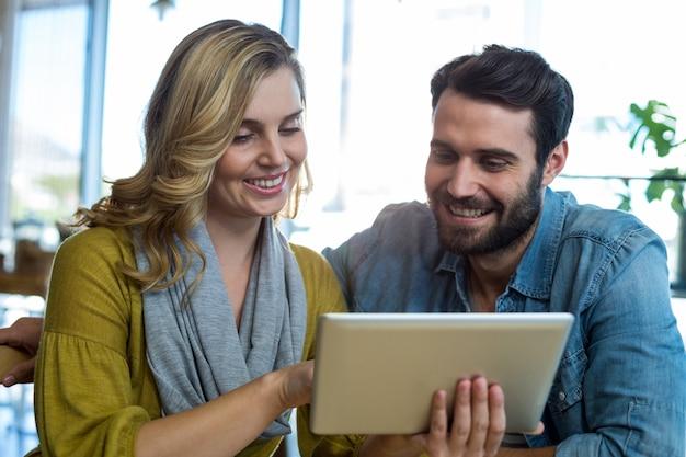 Casal usando tablet digital no café