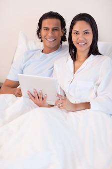 Casal usando tablet pc na cama