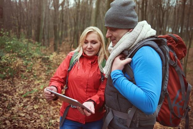 Casal usando tecnologia sem fio na floresta